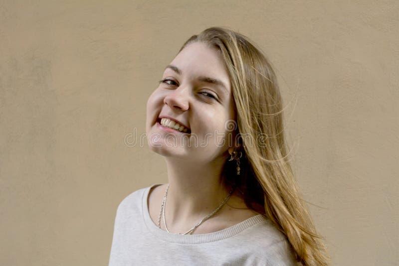 米黄背景的美丽的逗人喜爱的女孩 没有任何人 有嫉妒的白肤金发的女孩 她看照相机并且微笑 Busines 免版税库存照片