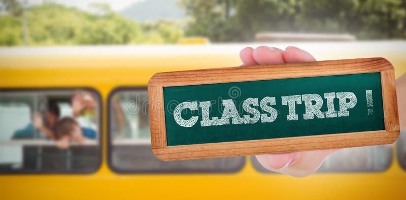 类旅行!反对微笑对照相机的逗人喜爱的学生在校车上 免版税库存图片