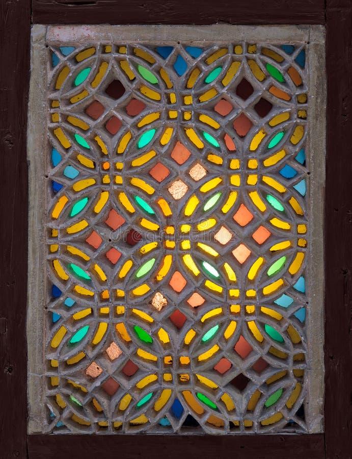 粉刷用与几何圆样式的五颜六色的污点玻璃装饰的窗口,无背长椅时代传统 免版税库存照片