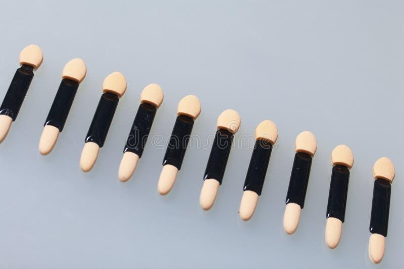 粉末应用的化妆棍子 溢出在桌的白色表面 在视图之上 免版税库存图片