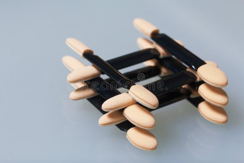 粉末应用的化妆棍子 被折叠的一个在一轻的桌表面上 免版税库存图片