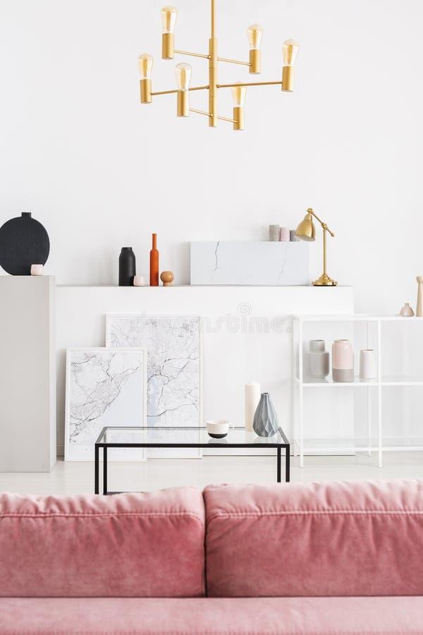 粉末桃红色沙发后侧方垂直的看法在白色现代客厅内部的与咖啡桌、金黄枝形吊灯和地图 免版税库存图片