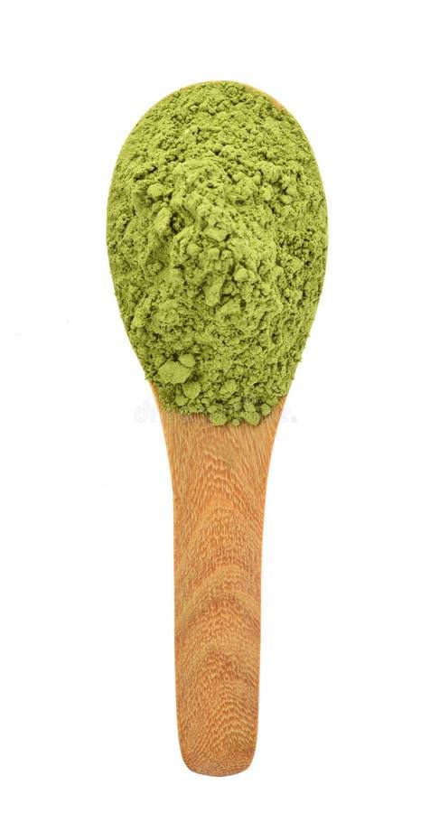粉末绿茶顶视图在白色背景隔绝的木匙子的 免版税库存图片