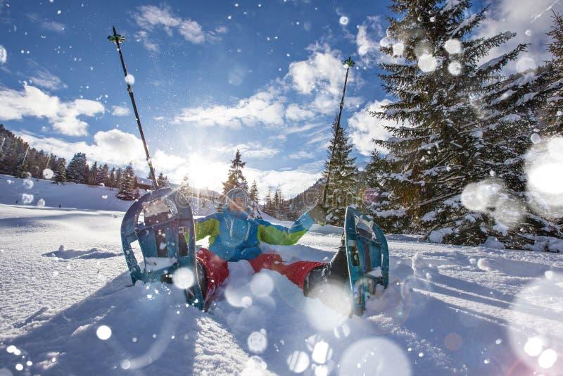 粉末雪的愉快的雪靴步行者与美丽的太阳发出光线 库存照片