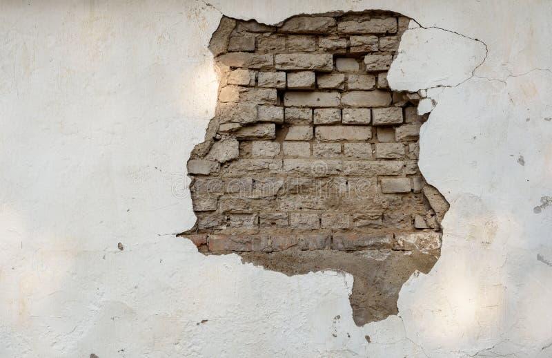粉碎的油漆工作和墙壁有被暴露的砖的 免版税库存照片
