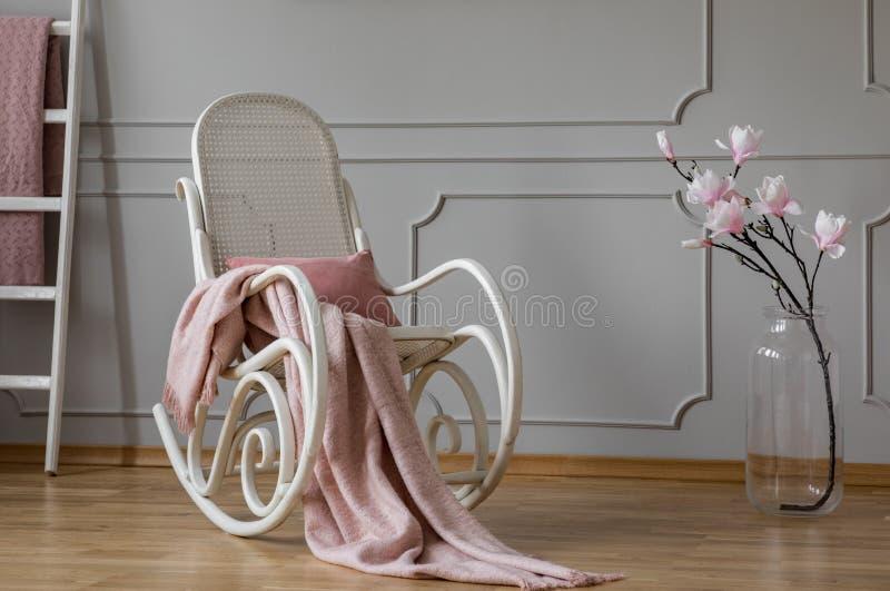 粉红彩笔毯子和枕头在白色摇椅在花旁边在玻璃花瓶,拷贝空间在空的墙壁上 免版税库存照片