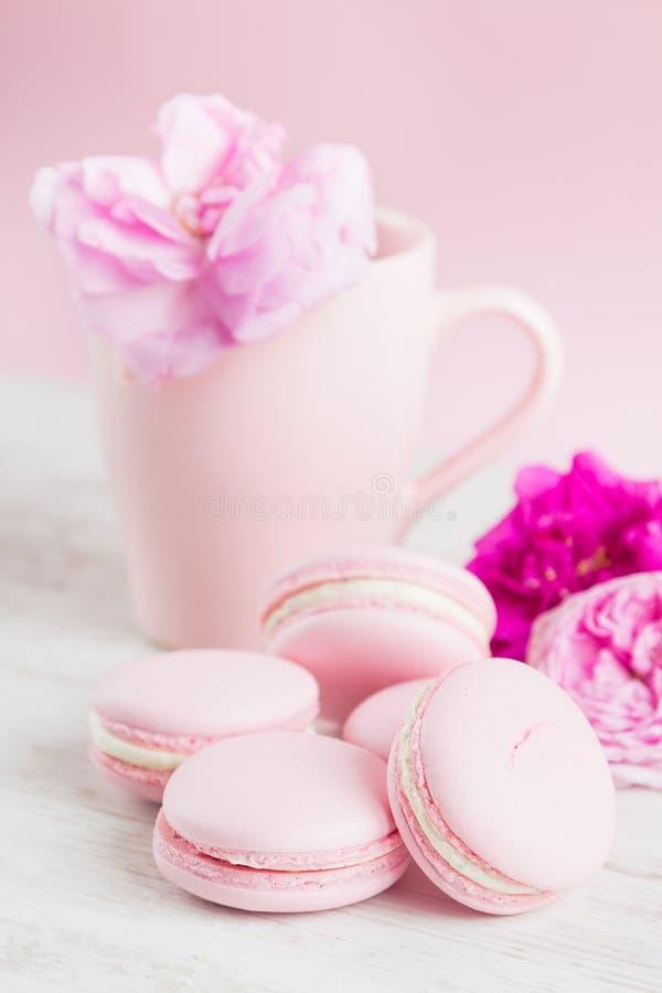 粉红彩笔蛋白杏仁饼干和茶杯与上升了 免版税图库摄影