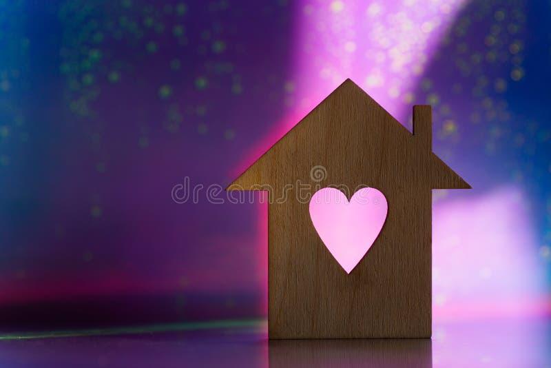 粉红色和紫色暗银河背景上带有心形洞的房屋的木质图标 免版税库存照片