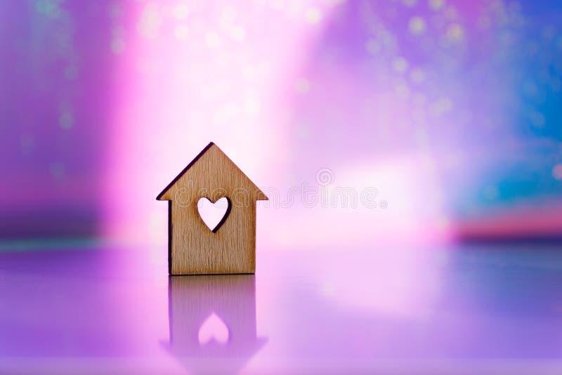 粉红色和紫色模糊银河系背景上带有心形洞的房屋的木质图标 免版税库存图片