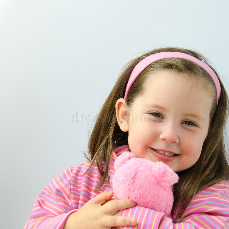 粉红色的俏丽的女孩拥抱她的玩具熊 免版税库存照片