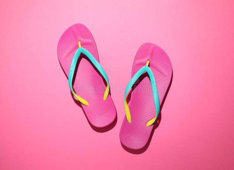 粉红色背景中的一对时尚的人字拖 海滩物体 库存图片