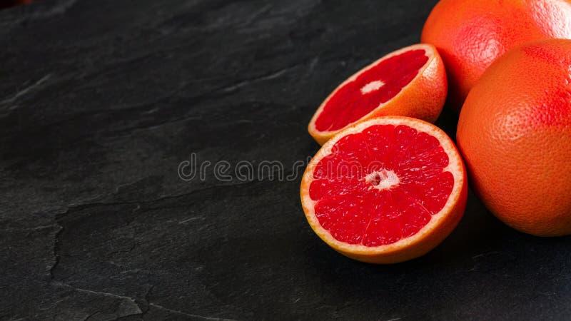 粉红色葡萄柚,一个柑橘在象委员会的黑板岩对分了,与空间的宽横幅文本左边的 免版税图库摄影
