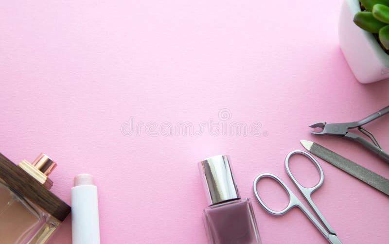 粉色口红、指甲油、粉色、香水瓶、修指甲剪刀、指甲锉、表皮少年和小的花在白色 库存照片