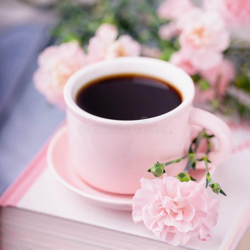 粉色的黑咖啡,书和粉色康乃馨花 免版税库存照片