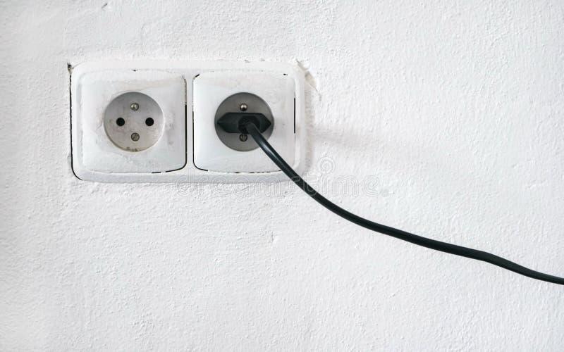 粗砺的有两个欧洲风格的电源输出口的门面白色墙壁,一个插口塞住了黑缆绳 免版税库存照片