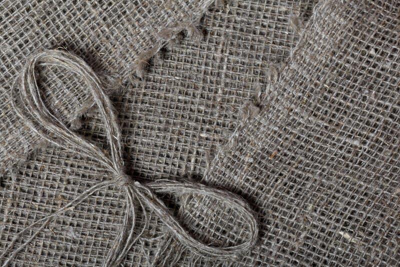 粗糙的亚麻制织品 它说谎亚麻制螺纹弓  库存照片