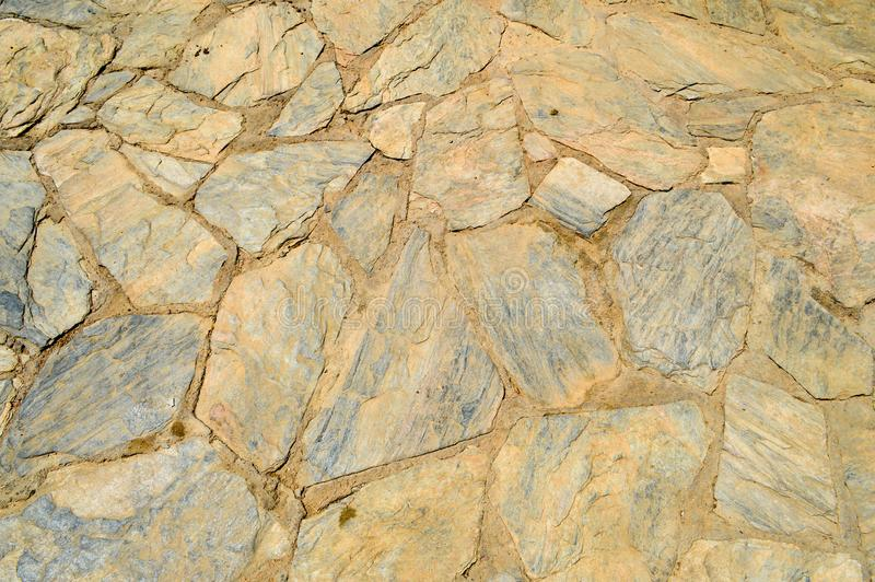 粗糙的老,古老褐色纹理被雕刻的参差不齐的石头,有缝合的鹅卵石在bristchatku的地板放置了 库存照片