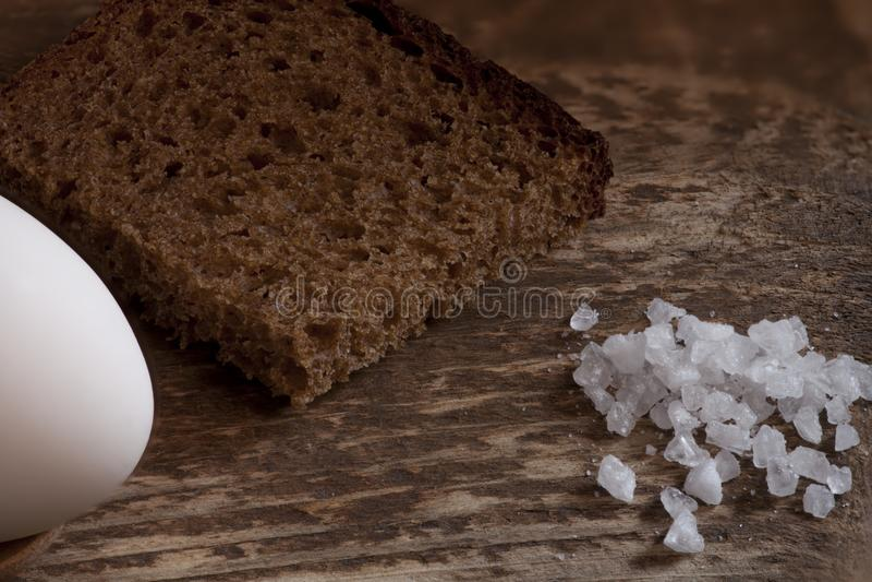 粗糙的黑麦面包片断与盐和鸡蛋的 库存照片