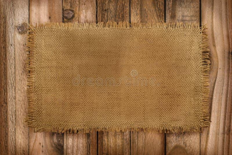 粗麻布材料土气背景在一张木桌上的与拷贝 免版税库存照片