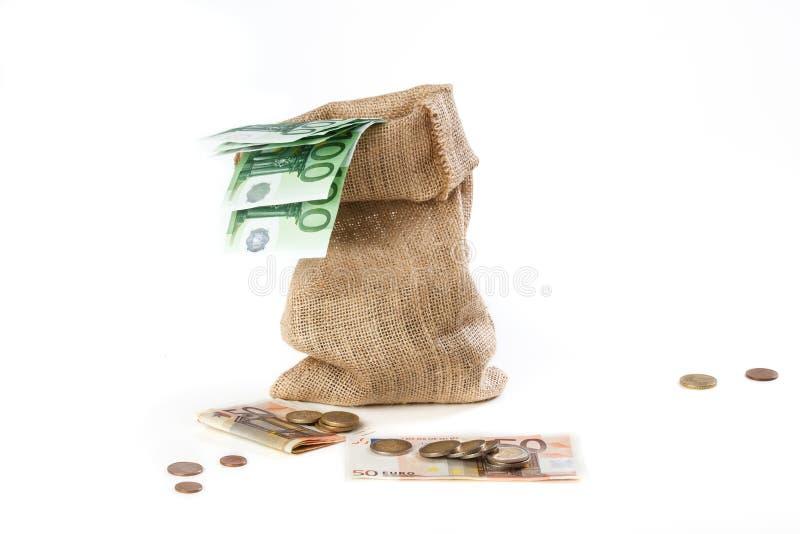 粗麻布大袋用欧洲钞票和硬币填装了,在wh 免版税图库摄影