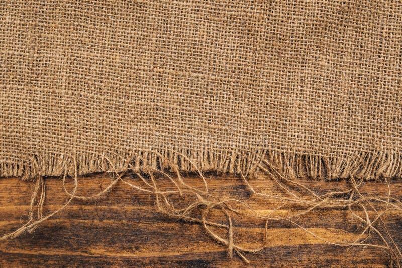 粗麻布黑森州袋装在木背景 免版税库存照片