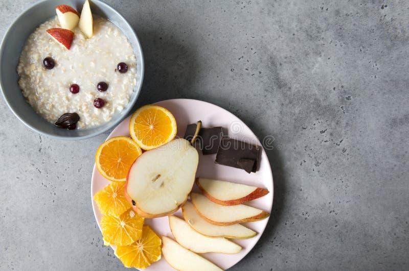 粥板材用梨,半梨,蔓越桔莓果,巧克力片,在板材的橙色切片莓果和片断, 图库摄影