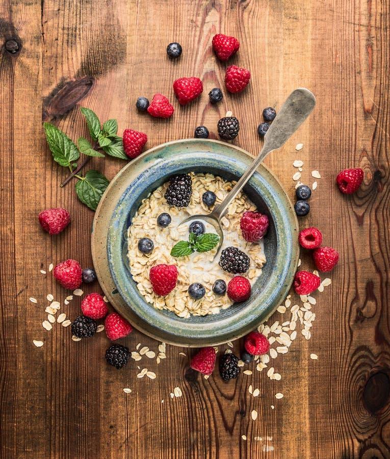 粥用牛奶,在土气碗的莓果在木背景,顶视图 免版税库存照片