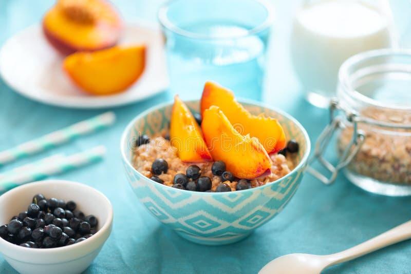 粥碗燕麦粥用桃子和蓝莓在绿松石背景 r E 图库摄影