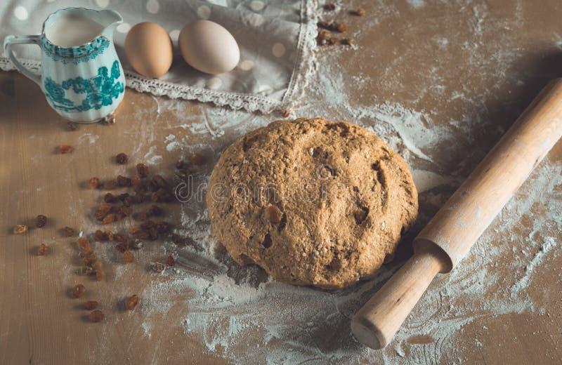 粮仓与面粉打扫灰尘的面团和辗压别针、鸡蛋和牛奶在木桌上在面包店关闭 免版税图库摄影
