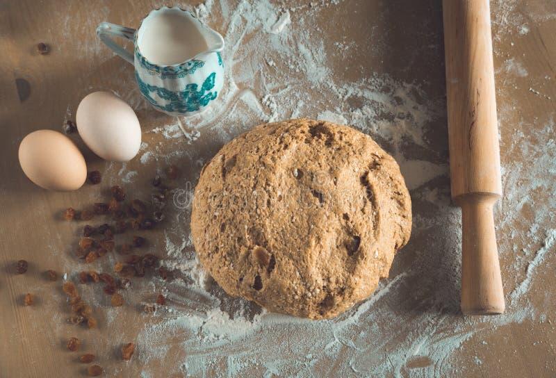 粮仓与面粉打扫灰尘的面团球和辗压别针、鸡蛋和牛奶在木桌上在面包店关闭 免版税库存照片