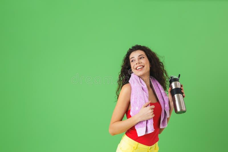 精力充沛的妇女20s的图象运动服高兴的和饮用水的在训练以后 图库摄影