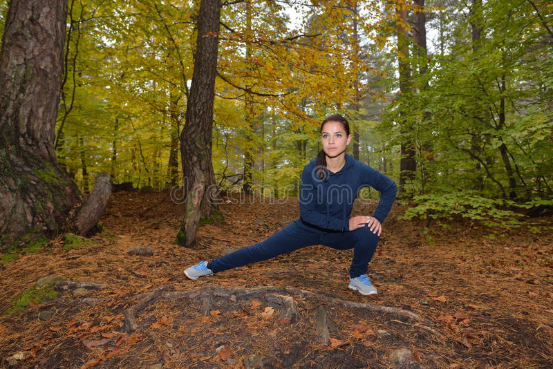 精力充沛的少妇在公园做锻炼户外 体育心情 免版税库存图片