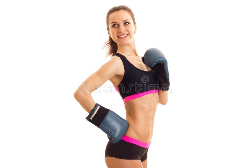 精力充沛的微笑的运动员在拳击手套和上面站立 免版税库存照片