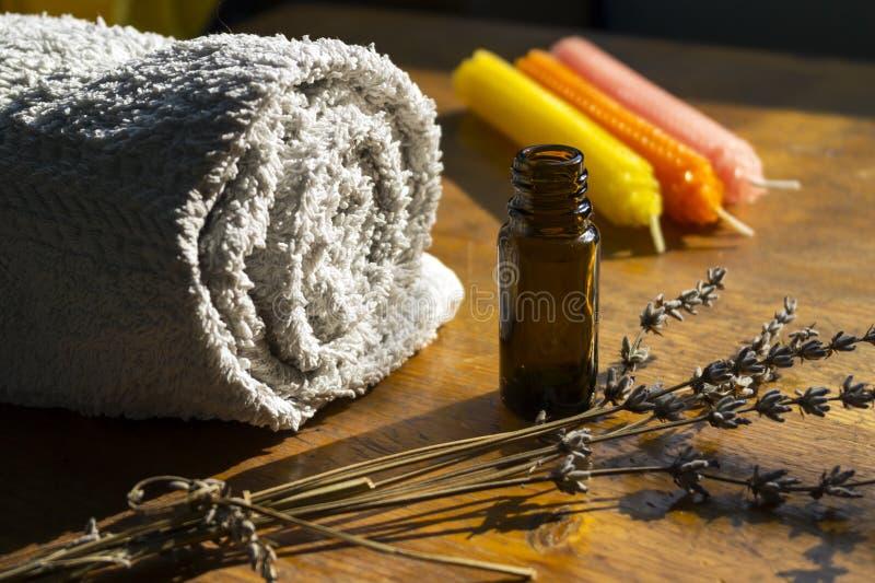 精华温泉瓶、毛巾和蜡烛 免版税图库摄影