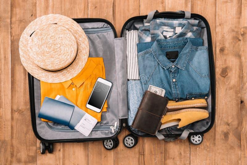 精华顶视图游人的有衣裳、辅助部件和小配件的,钱包,护照,在袋子的智能手机 库存照片