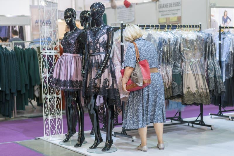 精品店的妇女选择衣裳 购物在时尚购物中心的妇女,选择新的衣裳 图库摄影
