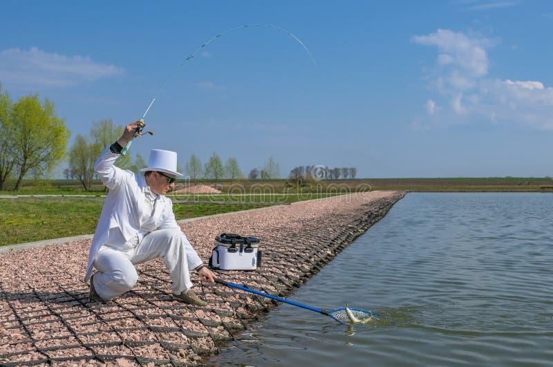 精妙的钓鱼 白色衣服抓住鱼的渔夫由在鳟鱼区域湖的实心挑料铁杆 免版税库存图片