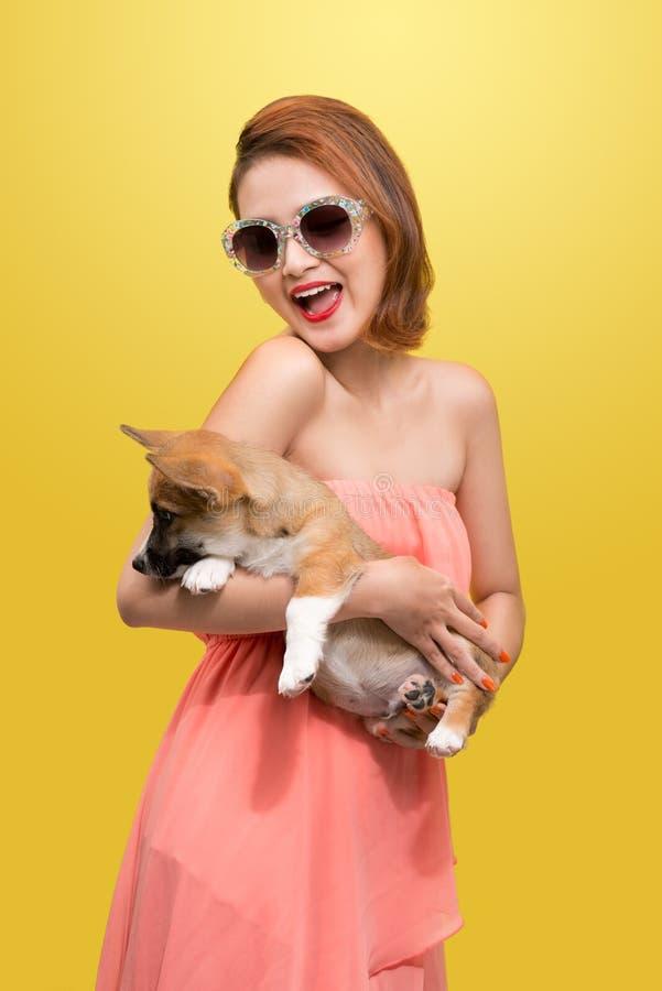 精密春天礼服的美丽的年轻亚裔妇女,摆在有小狗小狗的演播室 床单方式放置照片诱人的白人妇女年轻人 图库摄影