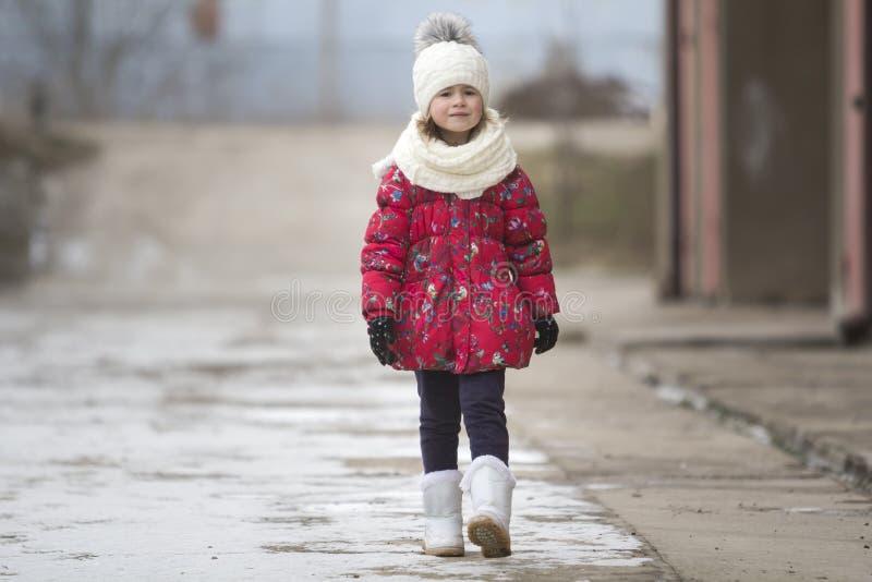 精密温暖的冬天衣物的单独确信地走在白色明亮的blurr的逗人喜爱的矮小的年轻滑稽的俏丽的儿童女孩画象  库存照片