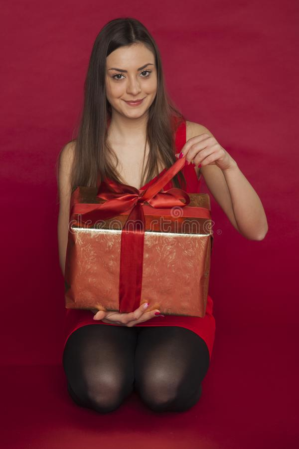 精密红色礼服的妇女在她的手上拿着一件礼物 库存照片