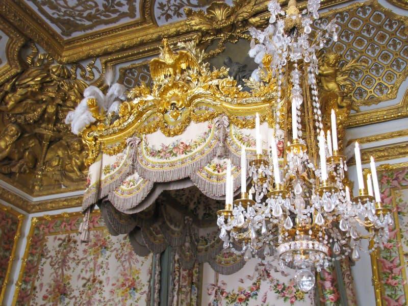 精心制作的枝形吊灯和床细节在凡尔赛 免版税库存图片
