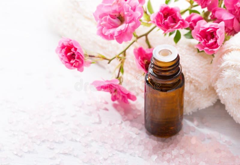 精油,矿物腌制槽用食盐,小桃红色玫瑰分支在木桌上的 免版税库存照片