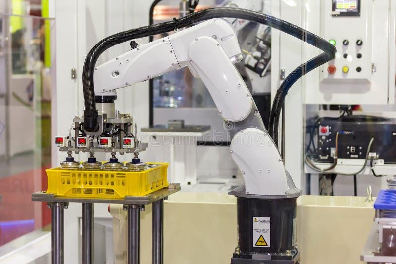 精确度和准确性在工作被投入的玻璃瓶期间的产业机器人胳膊高技术在有自动的塑料盒 免版税库存图片