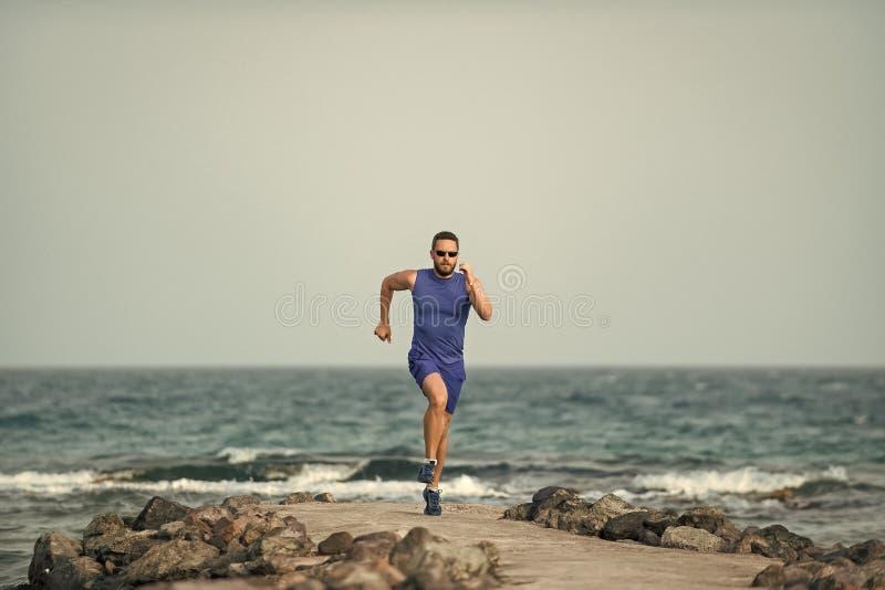 精神愈合身体关心 跑在蓝天的海海滩的赛跑者人 免版税库存图片