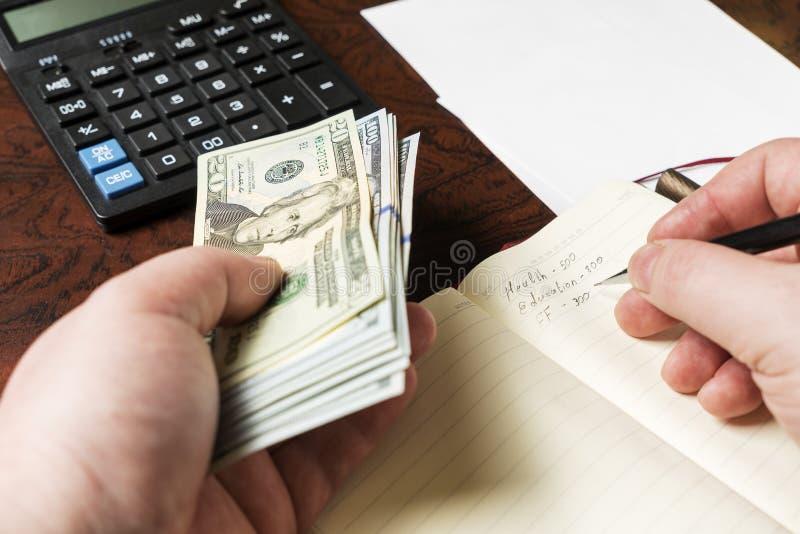 精神手拿着美元并且计数在计算器的费用 免版税库存照片