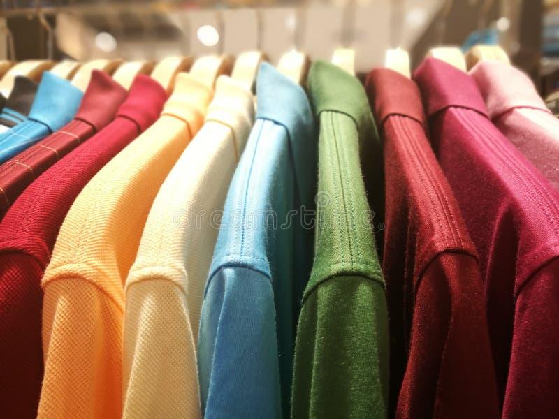 精神衬衣用在挂衣架的不同的颜色在零售给s穿衣 免版税库存图片