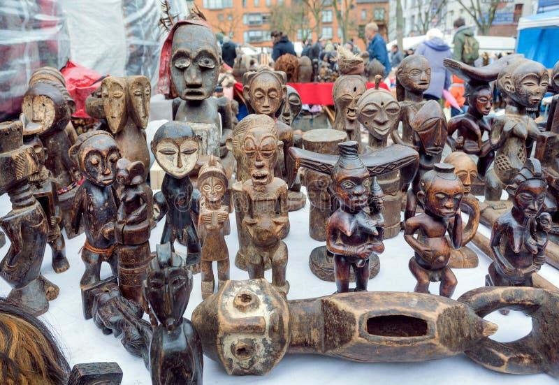 精神许多非洲图腾形象待售在与古色古香的材料和葡萄酒装饰的跳蚤市场 库存图片
