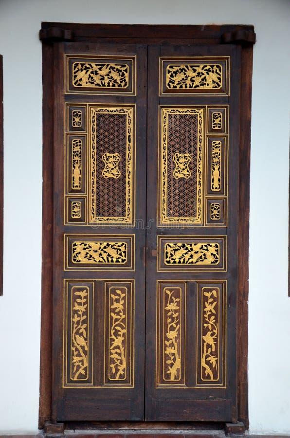 精美与金镶嵌槟榔岛马来西亚的Peranakan木头被雕刻的门 免版税库存图片