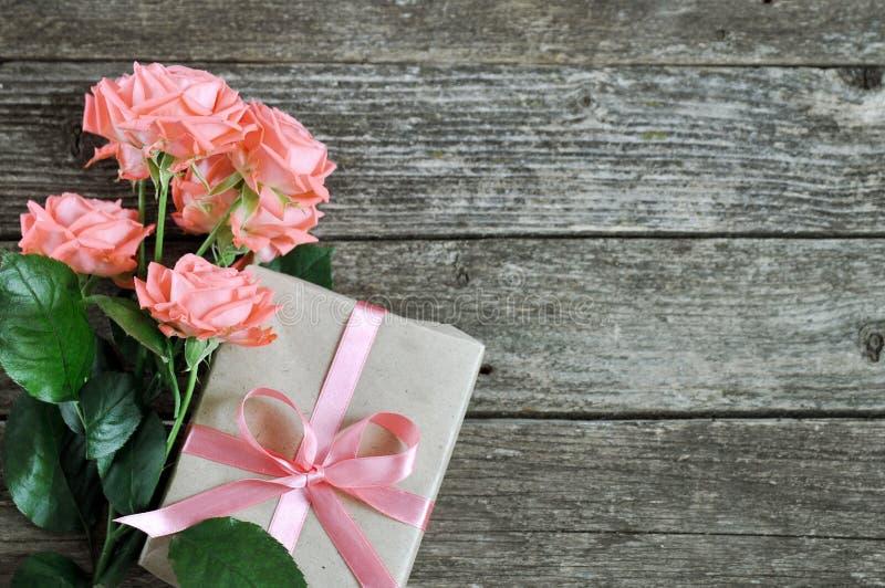 精美珊瑚树荫桃红色玫瑰和礼物在土气木背景 背景美好的例证华伦泰向量 妇女的假日卡片 库存图片