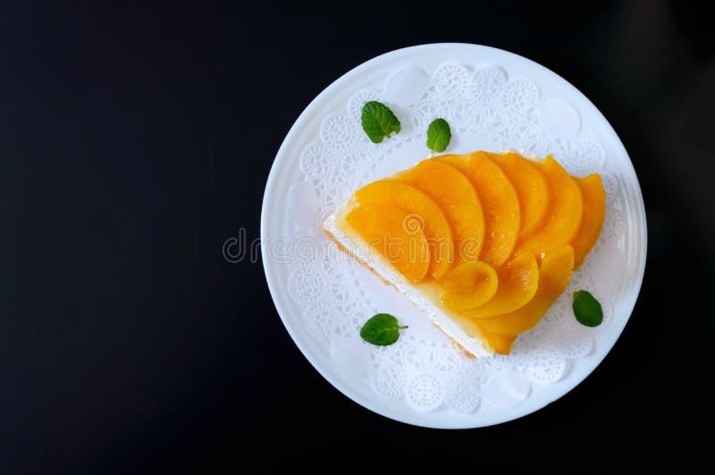 精美蛋白牛奶酥用水多的桃子 一块大可口蛋糕 免版税库存图片